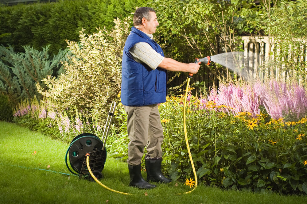 gardener watering plants - Big Easy Landscaping